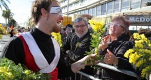 Un animateur de la BAT offre une tige de mimosa au public