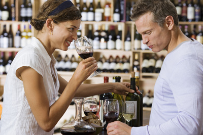 Couple wine tasting in off-licence, woman smelling glass of red wine, man drinking